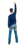 Vue arrière de l'homme A soulevé son poing dans le signe de victoire Photographie stock