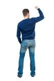 Vue arrière de l'homme A soulevé son poing dans le signe de victoire Photographie stock libre de droits