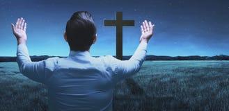 Vue arrière de l'homme soulevant la main tout en priant à un dieu Photographie stock