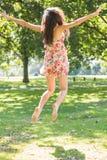 Vue arrière de la belle brune élégante sautant dans le ciel photo libre de droits