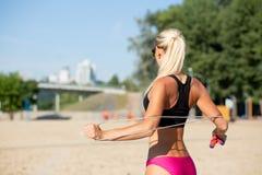 Vue arrière de la belle fille de forme physique faisant l'étirage à établir avec une corde de saut à la plage photo libre de droits