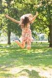 Vue arrière de la brune élégante attrayante sautant dans le ciel image stock