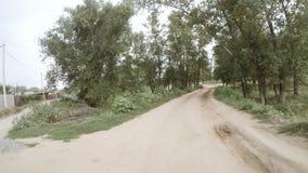 Vue arrière de la conduite le long d'un chemin de terre rural banque de vidéos