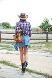 Vue arrière de la cow-girl de femme avec le sac à dos marchant sur le ranch images stock