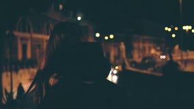 Vue arrière de la femme attirante de brune marchant tard la nuit La fille attirante passe par seul le centre de la ville banque de vidéos