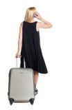 Vue arrière de la femme avec la valise parlant au téléphone Photographie stock libre de droits