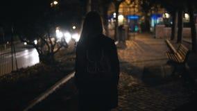 Vue arrière de la femme de touristes avec le sac à dos marchant par le parc foncé près de la route tard la nuit seul Images stock