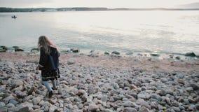 Vue arrière de la fille marchant sur le rivage Petite fille faisant des étapes incertaines sur les pierres, allant à l'eau banque de vidéos