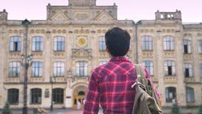 Vue arrière de la jeune étudiante avec les cheveux noirs courts marchant à l'université, femme allant à la journée d'université banque de vidéos