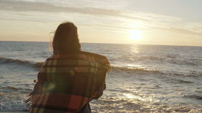 Vue arrière de la jeune femme avec le plaid appréciant le coucher du soleil sur la plage venteuse avec les bras étirés Concept de clips vidéos