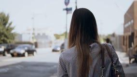Vue arrière de la jeune femme de brune marchant par le centre ville occupé à New York, Amérique dans le jour ensoleillé Mouvement banque de vidéos