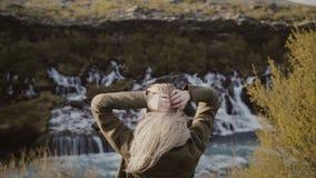 Vue arrière de la jeune femme de déplacement se tenant en vallée de montagnes et regardant sur des cascades seul en Islande banque de vidéos