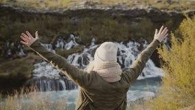 Vue arrière de la jeune femme de déplacement soulevant des mains et appréciant la belle vue des cascades en Islande banque de vidéos