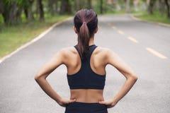 Vue arrière de la jeune femme de forme physique courant sur la route pendant le matin image libre de droits