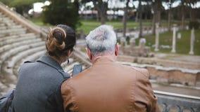 Vue arrière de la jeune fille européenne heureuse s'asseyant ainsi qu'un homme plus âgé parlant aux ruines de l'amphithéâtre d'Os banque de vidéos