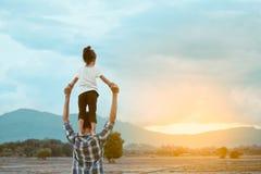 Vue arrière de la petite fille asiatique se tenant sur l'épaule du ` s de père Photo libre de droits