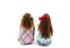 Vue arrière de la petite fille deux s'asseyant sur le plancher et recherchant Images stock