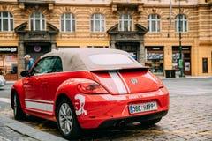Vue arrière de la voiture rouge de cabriolet de Volkswagen New Beetle garée dans la rue Image stock