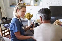 Vue arrière de membre du personnel soignant féminin mesurant la tension artérielle de l'homme supérieur pendant une visite à la m images libres de droits
