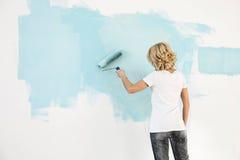 Vue arrière de mur de peinture de femme avec le rouleau de peinture Images libres de droits