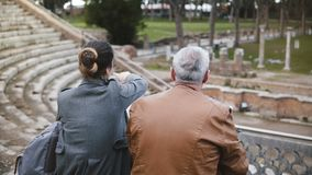 Vue arrière de père européen et de fille s'asseyant et parlant à de vieilles ruines d'amphithéâtre antique d'Ostia en Italie banque de vidéos