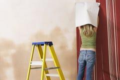 Vue arrière de papier peint accrochant de femme image stock