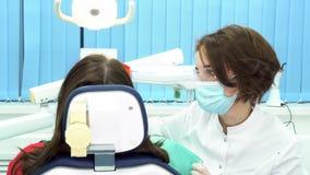 Vue arrière de patient féminin se reposant dans la chaise dentaire recevant une injection au dentiste Media Fabrication de femm banque de vidéos