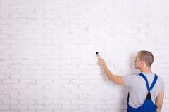 Vue arrière de peintre de l'homme dans le mur de briques de peinture de vêtements de travail avec du Br Image libre de droits