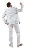 Vue arrière de penser le jeune homme d'affaires dans le costume blanc. Image libre de droits