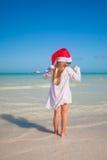 Vue arrière de petite fille mignonne dans le chapeau rouge Santa Image libre de droits