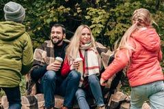 vue arrière de petits enfants mignons courant aux parents heureux buvant du café image libre de droits
