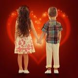Vue arrière de petits enfants tenant des mains Image stock