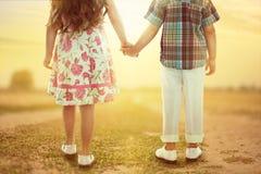 Vue arrière de petits enfants tenant des mains au coucher du soleil Images libres de droits