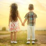 Vue arrière de petits enfants tenant des mains au coucher du soleil Photos libres de droits