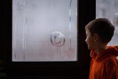 Vue arrière de peu de sourire drawning d'enfant sur le verre embrumé regardant par la fenêtre photographie stock