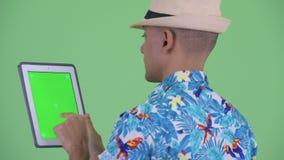 Vue arrière de plan rapproché d'homme de touristes ethnique multi heureux utilisant le comprimé numérique banque de vidéos