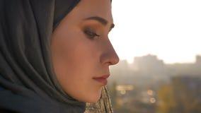 Vue arrière de plan rapproché de jeune femelle attirante dans le hijab regardant en avant la ville urbaine tournant et regardant  clips vidéos