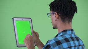 Vue arrière de plan rapproché de jeune homme africain heureux de hippie utilisant le comprimé numérique banque de vidéos