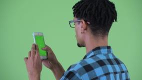 Vue arrière de plan rapproché de jeune homme africain heureux de hippie utilisant le téléphone banque de vidéos