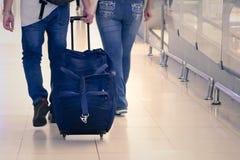 Vue arrière de prise de bagage de voyage sur la main de passager à l'aéroport Photographie stock libre de droits