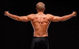 Vue arrière de sportif musculaire sexy avec des bras étirés  Photos stock