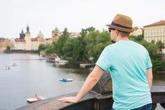 Vue arrière de touriste élégant heureux sur Charles Bridge, Prague, République Tchèque Homme bel voyageant en Europe Images stock