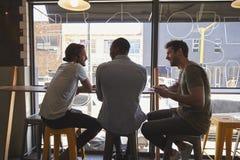 Vue arrière de trois amis masculins se réunissant dans le café images libres de droits