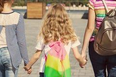 Vue arrière de trois enfants de ` de filles Ils tiennent les mains, promenade dans la ville Image libre de droits