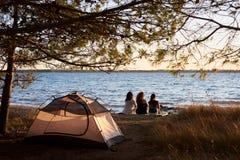 Vue arrière de trois filles de touristes s'asseyant sur le rivage de lac devant la tente appréciant le beau coucher du soleil Photographie stock libre de droits