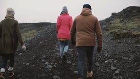 Vue arrière de trois personnes trimardant dans les montagnes Groupe des jeunes marchant ensemble, appréciant l'Islande banque de vidéos