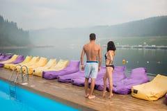 Vue arrière de type avec l'amie près de la piscine luxueuse de station de vacances appréciant le paysage parfait de belles vues Photos stock