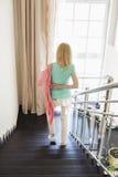 Vue arrière de veste de port de femme tout en abaissant des étapes à la maison Photos stock
