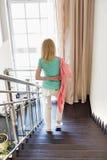 Vue arrière de veste de port de femme tout en abaissant des étapes à la maison Photographie stock libre de droits