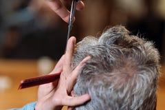 Vue arrière de vieil homme pendant la coupe de cheveux Photographie stock libre de droits